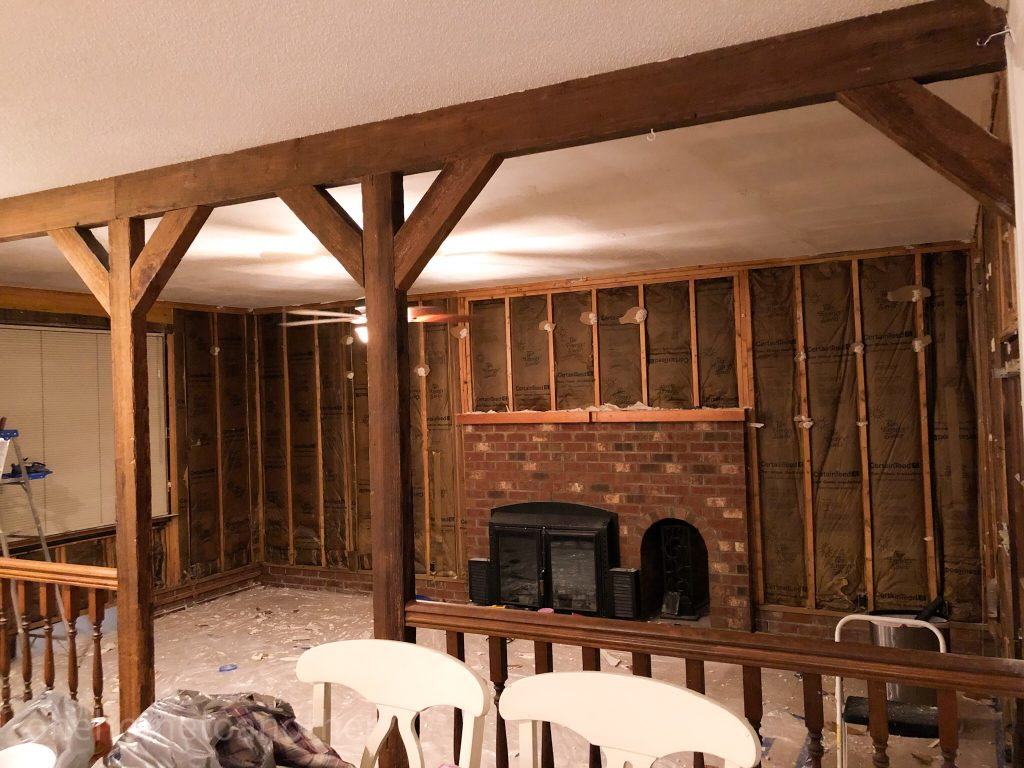 A view of our family room with the fireplace mantle taken off and the walls torn down to the studs.