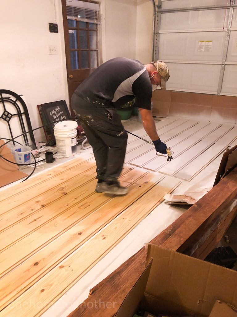 shiplap boards laid out and being spray painted to be hung on our family room walls.